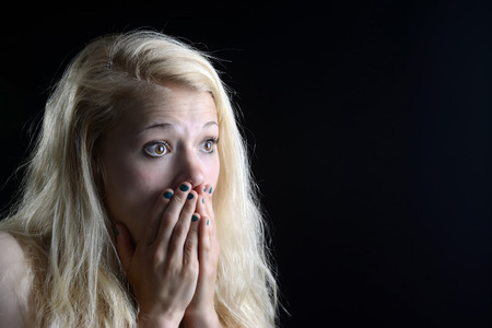 yelp: surprised young  woman in front of black background