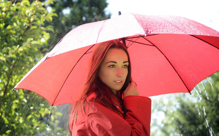 young woman with red umbrella standing in the rain photo
