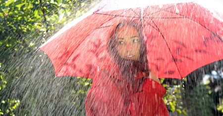 happy young woman with red umbrella standing in the rain photo