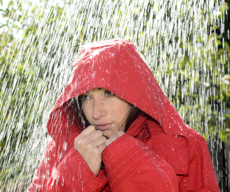 freezing young woman with hood standing in the rain photo