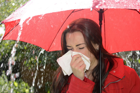 sneezing young woman with red umbrella standing in the rain photo