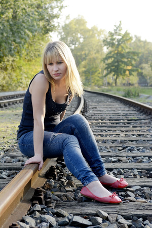 depressed young woman sitting on rail track