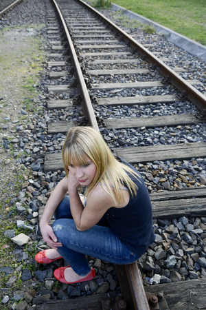 lovesickness: depressed young woman sitting on rail track