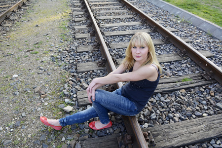 pretty young woman: pretty young woman sitting on rail track Stock Photo