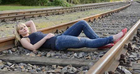 beautiful young woman lying on rail track