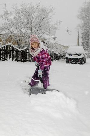 niño empujando: niña feliz con pala de nieve Foto de archivo