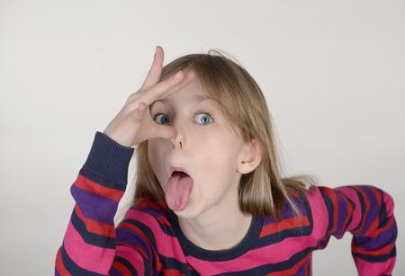 sacar la lengua: ni�a saca su lengua  Foto de archivo