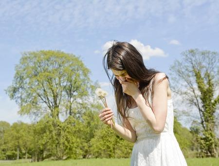 jonge vrouw niest op een bloem weide Stockfoto