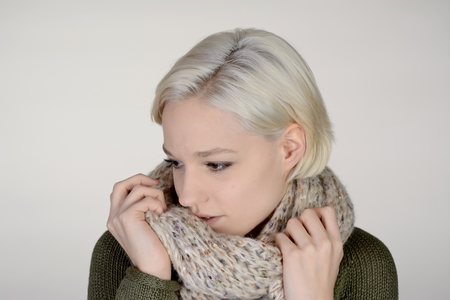 shivering: young woman with scarf , grey background