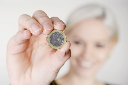 gratuity: happy young woman presenting one Euro