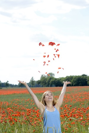 happy young blond woman throwing poppy blossoms