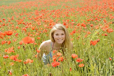 happy young blond woman in poppy field