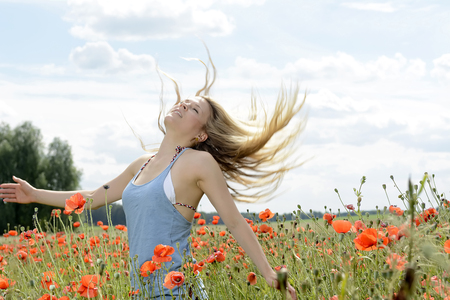 sensual young blond woman with flying hairs in poppy field