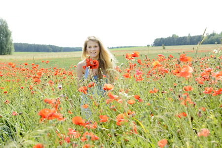 soulfulness: happy young blond woman in poppy field