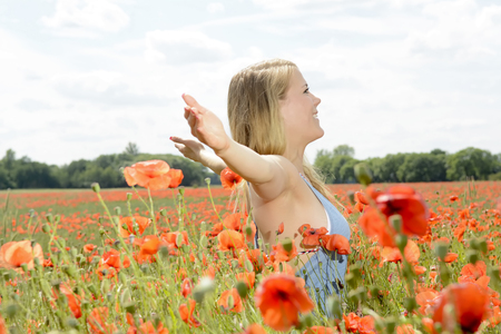 happy young blond woman cheering in poppy field Stock Photo