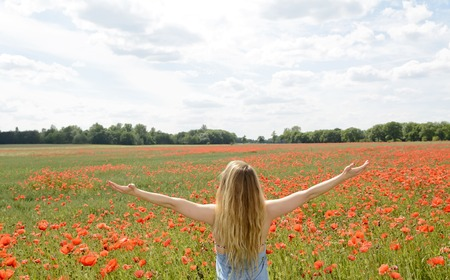 happy young blond woman cheering in poppy field , rear view