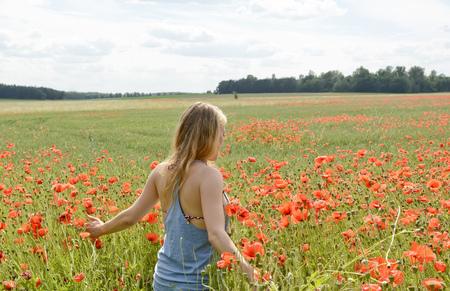 young blond woman walking in poppy field, rear view