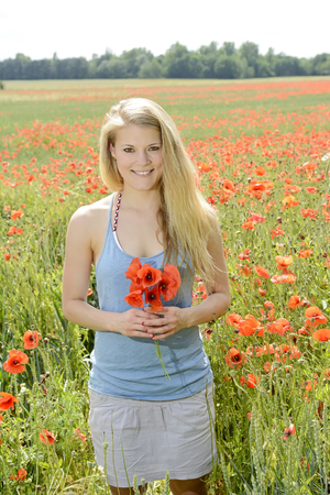 happy young blond woman with bouquet in poppy field