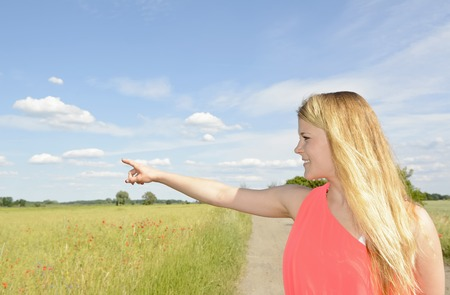happy young blond woman pointing with forefinger Stock Photo