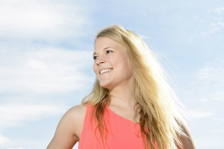 downtime:  happy young blond woman against blue sky Stock Photo