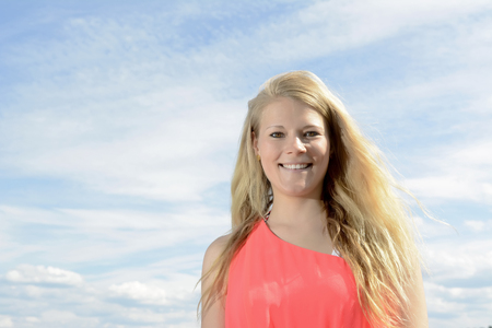 happy young blond woman against blue sky Stock Photo