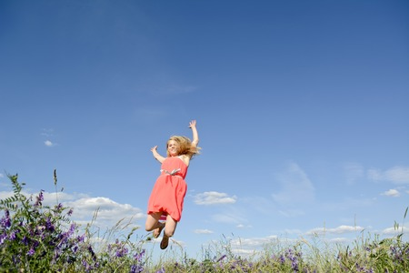 joyful young blond woman leaping