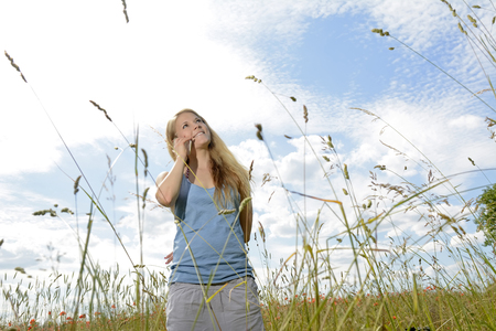 happy young blond woman with smartphone on  flower meadow Stock Photo
