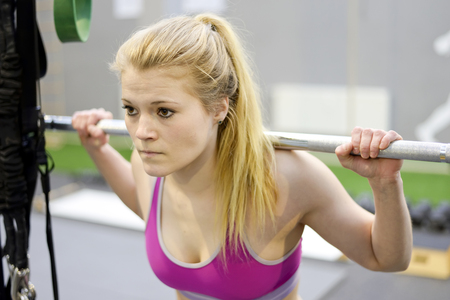 Young blond woman lifting weights in gym Stock Photo