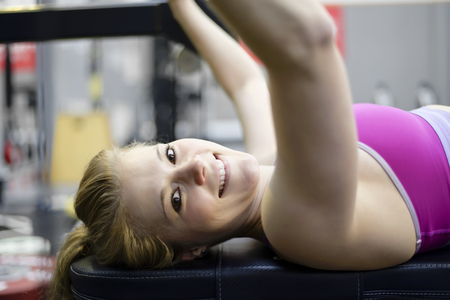 stemming: Young blond woman lifting weights in gym Stock Photo