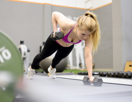 pushup: Young blond woman lifting weights in gym Stock Photo