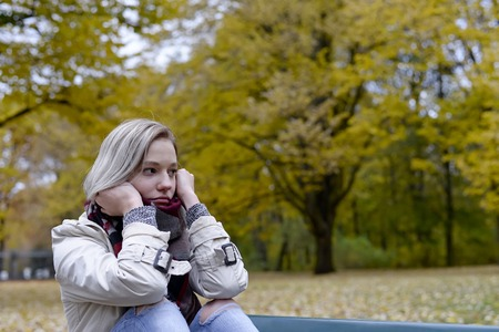 lonely young woman sitting on bench