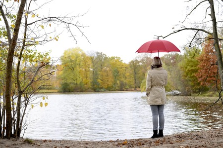 lonely young woman with umbrella standing on lake