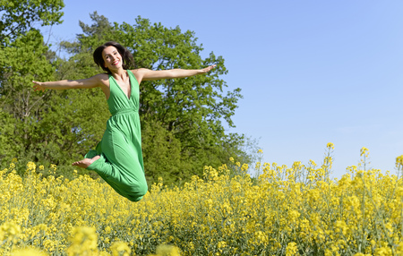 joyful young  woman leaping in the rape field Imagens