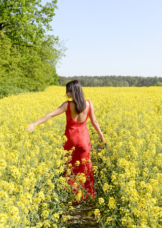 happy young woman  in the rape field, rear view