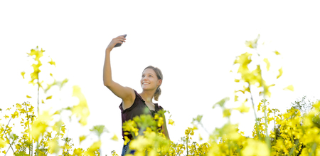 happy young blond woman taking selfie with smartphone