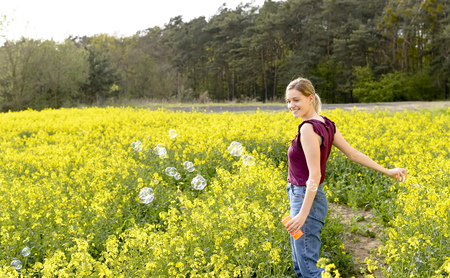 young woman making bubbles  in the rape field