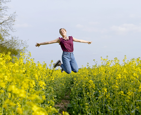joyful young  woman leaping in the rape field