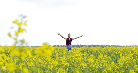 Young woman cheering in the rape field, rear view Stock Photo