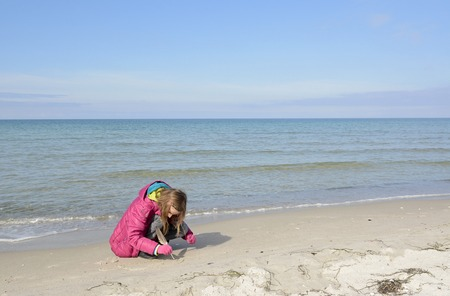 happy little girl with feather on the beach Stock Photo
