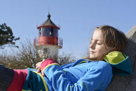 little girl sleeping in front of lighthouse