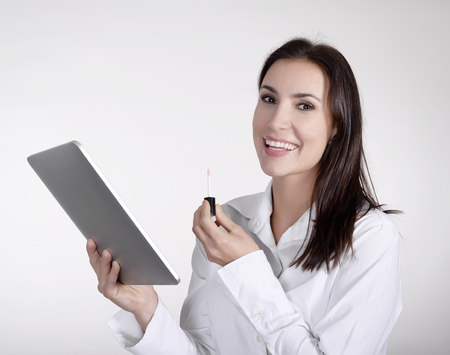 businesswoman with lipstick using digital tablet as a mirror