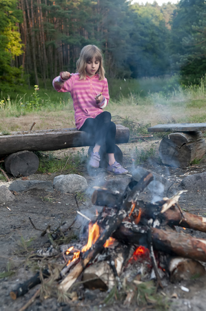 little girl carving on campfire
