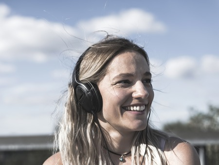 young blond woman with headphones Фото со стока
