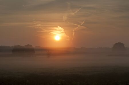 Sunrise over a field with morning mist Stok Fotoğraf