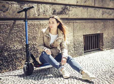 young woman sitting on  e-scooter
