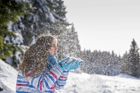 happy young girl blowing snow