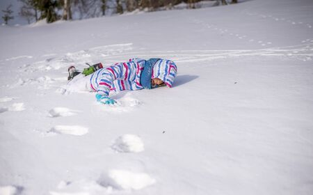 young girl falling in snow Stock Photo
