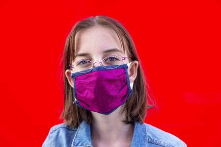 girl with mouthguard and glasses against red background