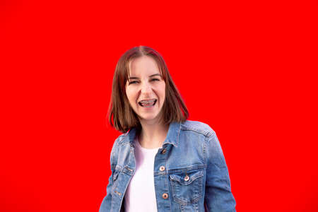 happy girl with braces against red background Stock Photo