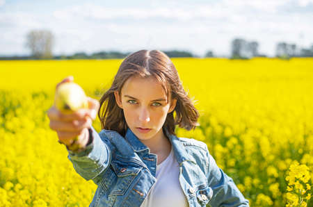 young girl with banana standing in rape field